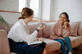 Een jongere en een therapeut zitten pratend op een bank