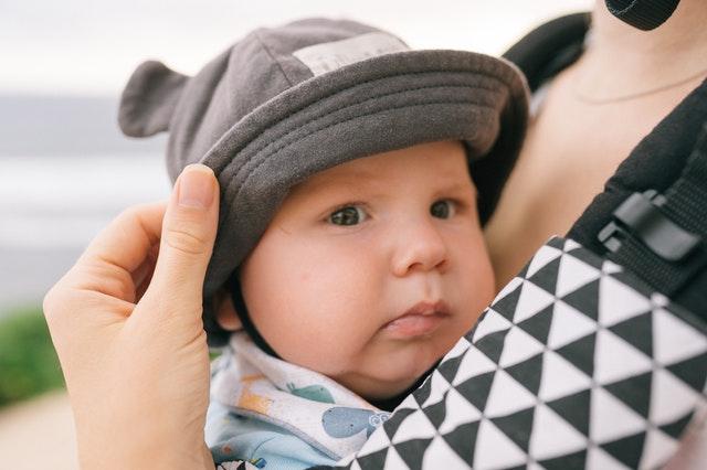 Een baby zit in een draagzak en kijkt in de camera