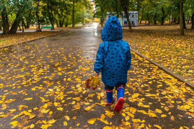 Een kind loopt door een park vol gevallen bladeren