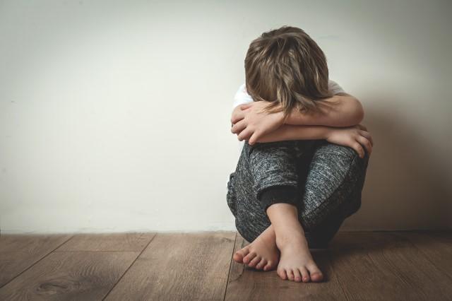 Een jongen in de basisschoolleeftijd zit op de vloer, tegen de muur aan, met opgetrokken knieën en met zijn hoofd in zijn armen