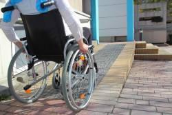 Persoon in rolstoel rijdt richting de ingang van een gebouw