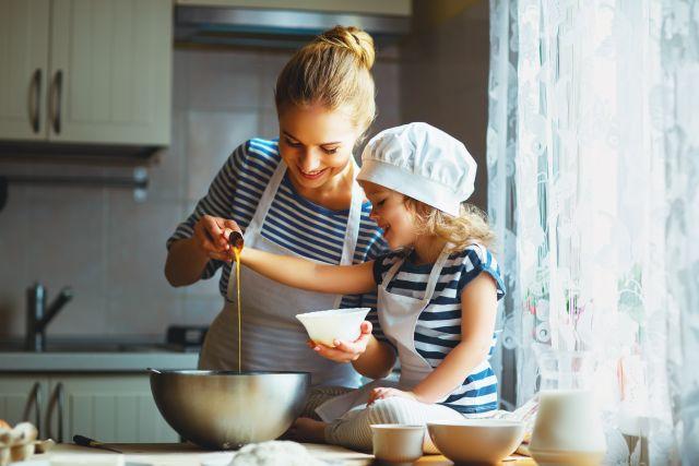 Foto van een moeder die samen met haar dochter aan het koken is