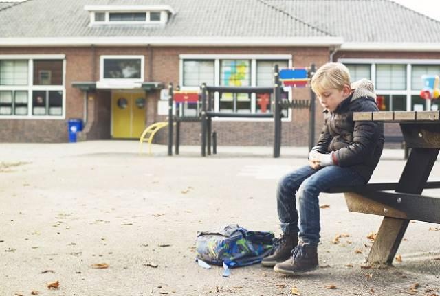 Foto van een jonge middelbare scholier die alleen op het schoolplein zit
