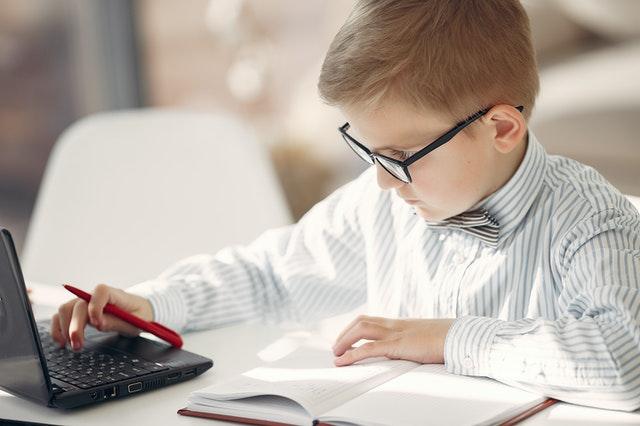Een kind van rond de 10 jaar oud kijkt door zijn bril naar een laptopscherm, met een opschrijfboek voor zich op tafel