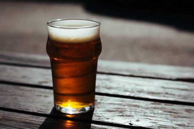 Een glas bier staat op een tafel