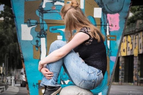 Een meisje zit met afgewend hoofd op een stenen paal