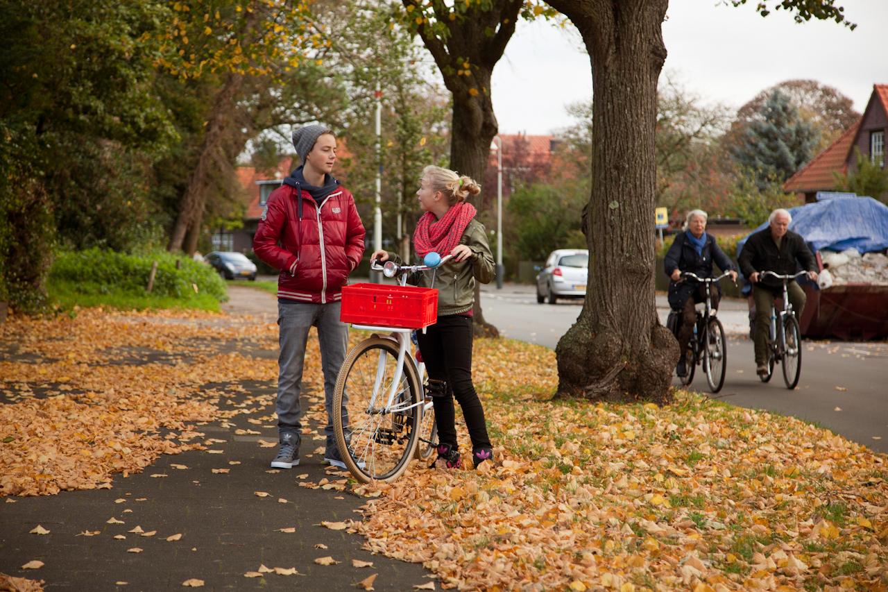 2 jongeren op een fietspad met gevallen bladeren op de weg.