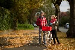 Een jongen en een meisje van rond de 15 jaar staan buiten te praten bij een fiets.