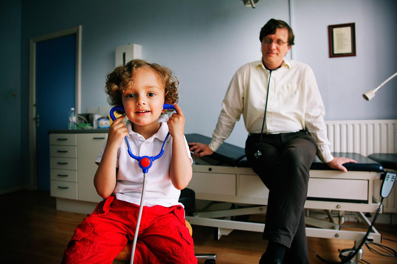 Een jongetje met een stethoscoop in zijn oren en de huisarts in de achtergrond