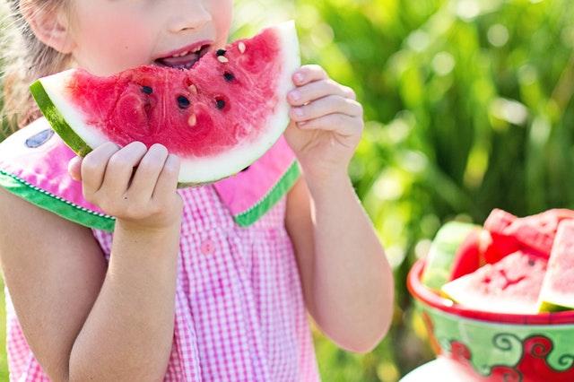 Foto van een meisje dat een watermeloen eet