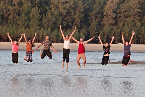 Een groep jongeren springt omhoog met de armen in de lucht