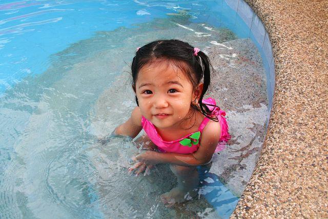 Foto van een meisje in een ondiep zwembad
